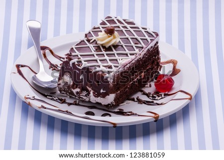 A small plate with chocolate cake consisting out of two layers.