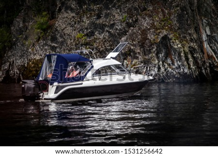 A small pleasure boat with a motor for excursions and relaxation in picturesque places on the water and traveling on a river or lake with tourists. Voyage, fishing and tourism.