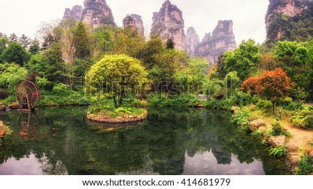 a small pond near gold whips tream in yangjiajie. Reflection of tall cliffs and mountain peaks on the pond.