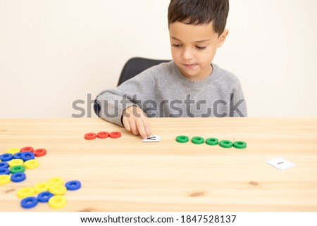 A small preschool child plays a math game, interested, focused. The topic of comparing numbers, concepts of more than, less than, equal to that, smart boy, early home schooling. Caucasian. Copy space. Stock photo ©