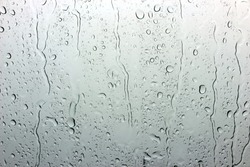 A small raindrop rests on the glass after rain.