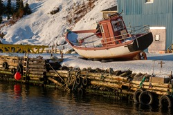 A small red and white wooden fishing boat on a wharf that is covered in white fresh snow. The wooden wharf has orange buoys and black rubber tires tied to it. Behind the boat is a mountain of snow.