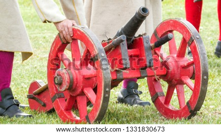 A small red cannon being dragged by the guards. The red cannon is one of the cannons on the park #1331830673