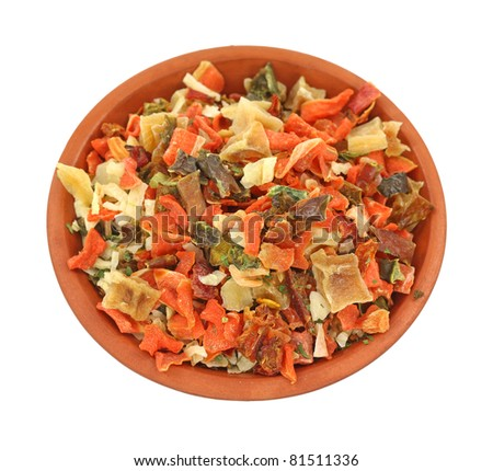 A small red dish filled with dried vegetable seasoning on a white background. - stock photo