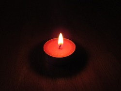 A small red tealight candle lit in a dark room on a table