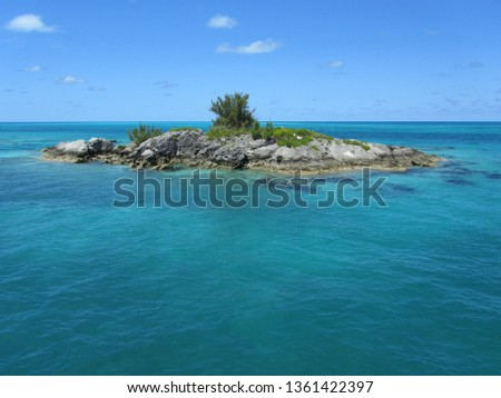 A small rocky island, with a little bit of green vegetation, surrounded by clear ocean water and blue sky with only a few small white clouds. #1361422397