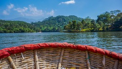 A small round shaped boat made with bamboo is floating over backwaters in Kerala. The lake is surrounded by greenery and mountains.