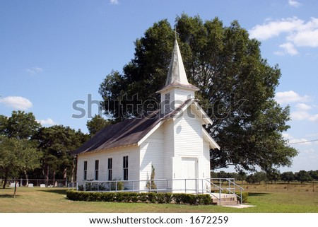 A small rural church in Texas.  There is a cemetary and a large oak tree behind the church.