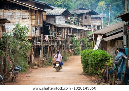 A small rural village, a hill tribe village in Chiang Mai Thailand, houses made of wood and bamboo, and a dirt road with a motorbike.