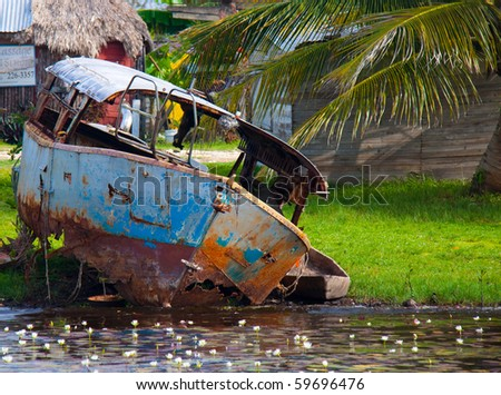 A small rusted, abandoned ferry in the town of Bomba, Belize