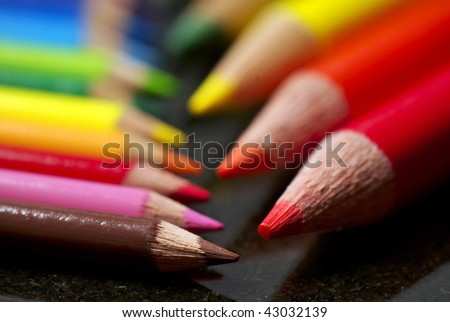 A small set of colored pencils faces a larger set, shallow depth of field.