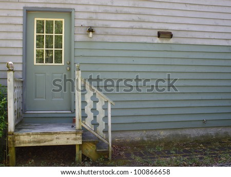 A small set of steps leading up to a small stoop and a doorway