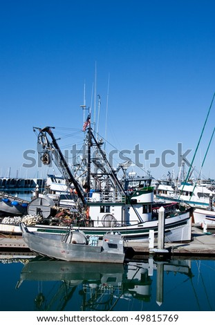 A small silver net boat docked by a large fishing trawler