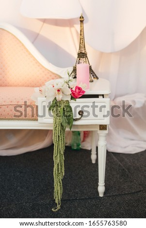 A small sofa in peach color, on which stands a souvenir of the Eiffel tower, a pink candle and a floral arrangement with orchids. Romantic wedding decor