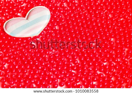 A small soft pastel colour heart pillow put on pile of red beads for background or