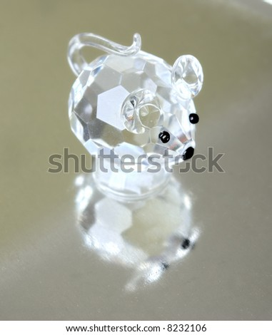 A small souvenir in the form of a glass mousy. Reflection from a metal ridge surface is visible.