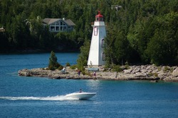 A small speedboat racing past an historical red and white wooden lighthouse on a perfect summer day.