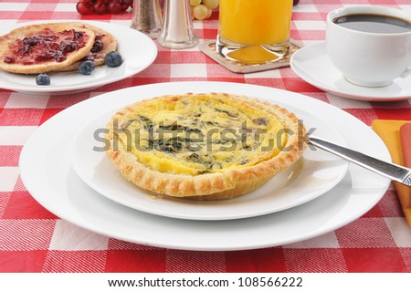 A small spinach quiche with toast and blueberry jam