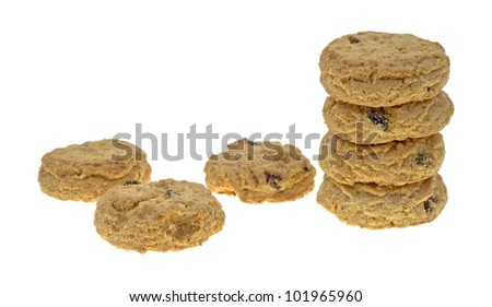 A small stack of oatmeal raisin cookies with three to the side on a white background.