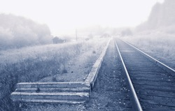 a small station on the railroad in the fog