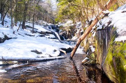 A small stream flowing down through Enders State Forest in Granby Connecticut on a sunny winter day.