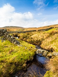 A small stream flows under a ruined dry stone wall in open moorland in winter. The imposing Dead Mans Hill is in the distance. Nidderdale. Blue skies and clouds make up the scene. Yorkshire Dales