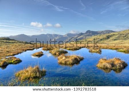 A small tarn on Silver Howe, a hill in the English Lake District, North West England. The Langdale Pikes and Bowfell in the distance.