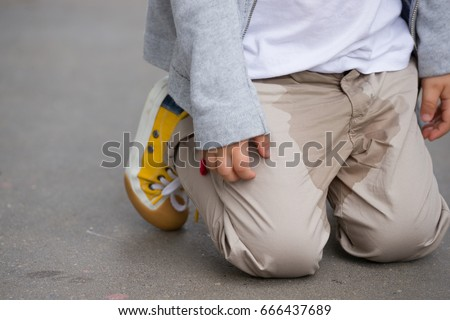 A  small toddler peeing on his pants on the street - Bed-wetting concept. Child pee on clothes. #666437689