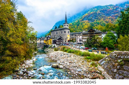 A small town by the river in the autumn mountains. Mountain forest river town. Small town in mountain forest.
