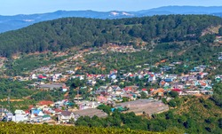 A small town under a tea hill valley in the morning in the highlands of Dalat, Vietnam. The place provides a great deal of tea for the whole country