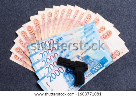 A small toy gun lies on a monetary background of five thousandths and two thousandths of Russian rubles. The concept of financial crime, the instability of the ruble, fraud