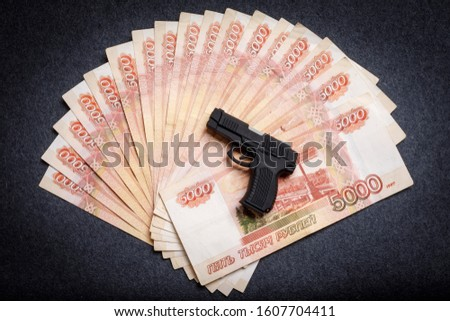 A small toy gun lies on a monetary background of five thousandths of Russian rubles. The concept of financial crime, the instability of the ruble, fraud.