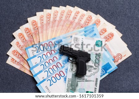A small toy gun lies on a monetary background of five thousandths, two thousandths and one thousandths of Russian rubles. The concept of financial crime, the instability of the ruble, fraud