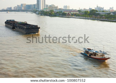 A small tugboat pulls a large barge up the Chao Phraya River in Bangkok, Thailand.