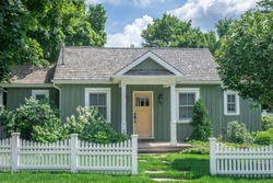 A small vintage cottage style home, in pastel green and yellow colours with white trim, set behind a white picket fence, surrounded by large mature trees, in a residential neighborhood.