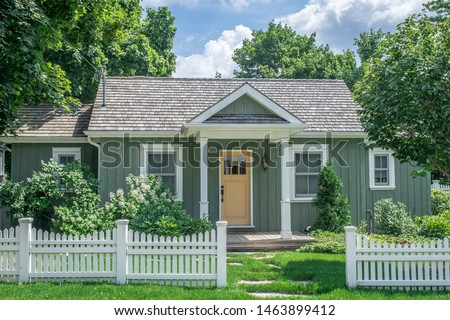A small vintage cottage style home, in pastel green and yellow colours with white trim, set behind a white picket fence, surrounded by large mature trees, in a residential neighborhood.  Foto stock ©