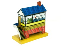 A small vintage Issmayer litho printed tinplate toy railway signal cabin on plain white background.