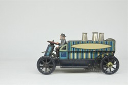 A small vintage litho-printed tinplate toy open delivery lorry by Whitanco with space for your logo or message to the side on a plain neutral backgound.