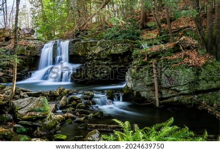 A small waterfall in the autumn forest. Waterfall in autumn forest. Autumn forest waterfall