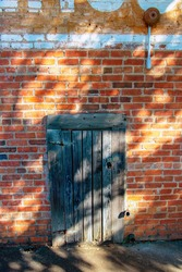 A small weathered wooden door in an old brick wall with faded paint and a vintage metal fire bell.