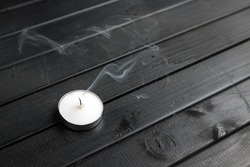 A small white candle on a dark wooden table. Smoke from a blown-out candle. Black tabletop boards. decorative candle.