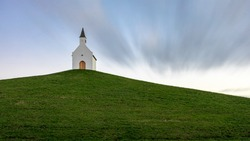 A Small white church on top of a grassy hill. It's a long exposure shot on a partly clouded day.