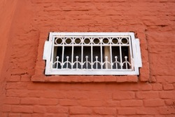 A small white window with bars on the red brick facade