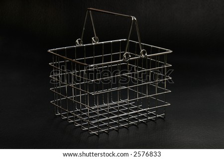 A small wire shoppping basket against on a black rubber background