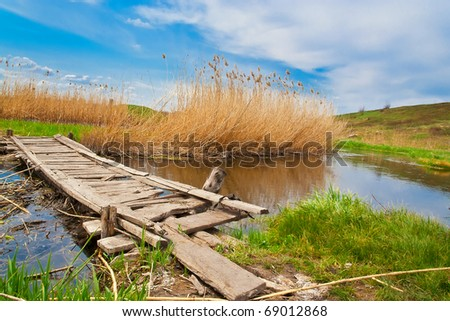 A small wooden bridge over a creek. Grass, blue sky, reeds
