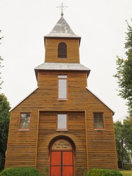 A small wooden brown Catholic Church with red doors in the village of Lithuania. Inscription above the door: Kuziu Saint Virgin Mary birth Church
