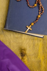A small wooden catholic cross on a wooden chain.