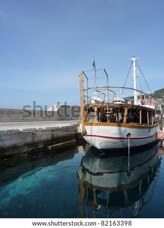 A small wooden cruise ship at the quay of the village Komiza at the island Vis in Croatia