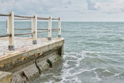 A small wooden pier for boating boats and ships against the backdrop of the blue sea with small waves.