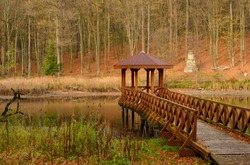 A small wooden pier, platform or jetty with a small gazebo with a slanted tiled roof at the end standing next to a vast yet shallow river or lake flowing through a dense forest or moor seen in Poland